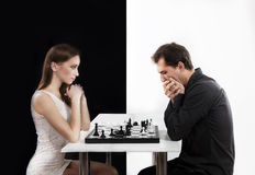 Competition between man and woman, concept. Man and women playing chess, black and white background stock images