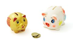 Competition and possession. Competition between two piggy banks over possession of coins Stock Photos