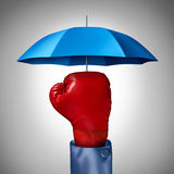 Competition Protection. Business concept with a red boxing glove from a businessman with a blue umbrella symbol protecting as a defense and buffer safeguard for Royalty Free Stock Image