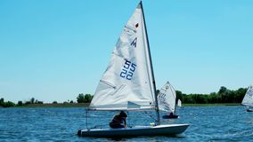 Competition sailing, rowing, local regatta on the river, a lot of boats appear before the audience, boats with sails,