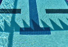 Competition swimming pool with backstroke flag shadows. Bright sunshine illuminates a competion swimming pool and creates shadows with the backstroke flags Royalty Free Stock Image
