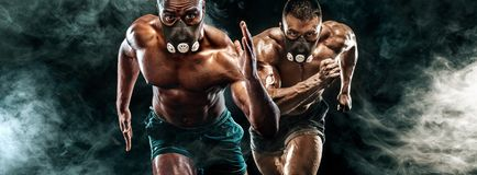 Competition of two strong athletic men sprinters in training mask, running, fitness and sport motivation. Runner concept with copy Stock Photo