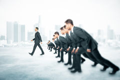 Competition walking businessman city. Competition concept with many businessmen about to run and one walking ahead of them on foggy city background Stock Image