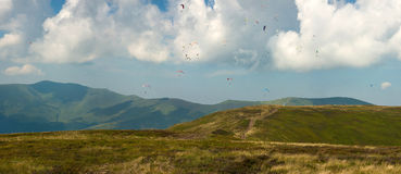 Competitions of paragliders on the ridge of Borzhava in the Carpathians in Ukraine. Panoramic photo of a large group of paragliders in the sky above the Royalty Free Stock Photography