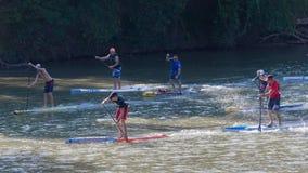 Competitiors nei quarti vicini in una corsa in piedi del bordo di pagaia Fotografia Stock