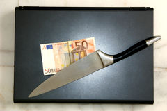 Competitive. A laptop with a knife and a fifty Euro note/bill on it depicting cut-throat business Royalty Free Stock Image