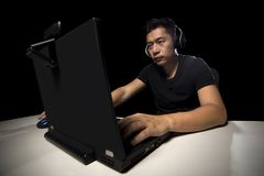 ESports Professional Competitive Gamer. Competitive asian male professional E Sports video gamer playing an FPS, or MMO game on a computer and streaming online royalty free stock images