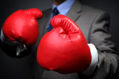 Competitive business. Tough competitive business concept businessman wearing boxing gloves royalty free stock photos