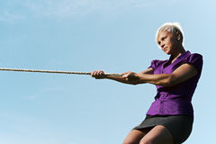 Competitive businesswoman playing tug of war with rope. Resolute business woman pulling rope against blue sky, symbol of power and determination. Copy space Stock Photos
