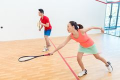 Competitive Chinese woman holding the racquet during a squash game. Side view of a beautiful and competitive Chinese women holding the racquet while looking Stock Photos