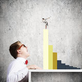 Competitive concept. Businessman screaming at businesswoman standing on top of graph Stock Image