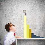 Competitive concept. Businessman screaming at businesswoman standing on top of graph Stock Images