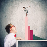 Competitive concept. Businessman screaming at businesswoman standing on top of graph Stock Photos