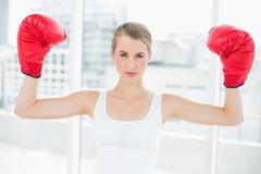 Competitive fit woman with red boxing gloves cheering up Royalty Free Stock Photography