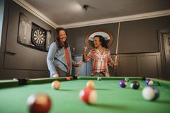 Competitive Friends Playing Pool. Two mid adult friends playing a game of pool in a games room in a house stock photos