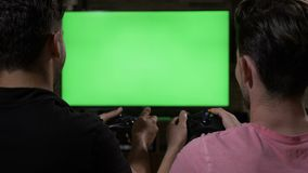 Competitive male friends enjoy playing video games with controllers watching at chroma key TV green screen at home -. Competitive male friends enjoy playing stock video footage