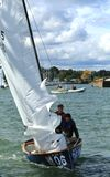 Competitive sailing in Lake Erie. Sailing crew raise the sail prior to the race at the United States Sailing Associations Championship of Champions Title at Lake Stock Images