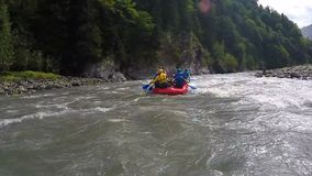 Competitive team rafting on boats through fast river torrent, extreme sports. Stock footage stock video footage