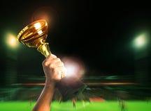 递在体育competiton的上升的足球橄榄球冠军杯子 免版税库存照片