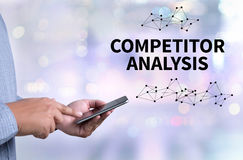 COMPETITOR ANALYSIS. Person holding a smartphone on blurred cityscape background stock images
