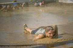 Competitor crawling through mud in obstacle course Stock Images
