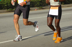 Competitors. White legs of a caucasian male athlete and black legs of an African American triathlete being competitors by running together in the Ironman Royalty Free Stock Photo
