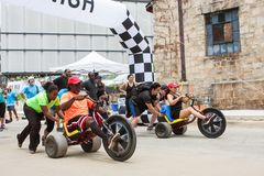 Competitors Race Adult Big Wheelsl In Atlanta Field Day Event. Atlanta, GA, USA - July 14, 2018: Competitors for two separate teams both get a push at the start stock images