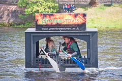 Competitors in  River Ness raft race. Green home Stoves taking part in  River Ness Raft race in aid of the Charity Children 1st held on 16th August 2014 Royalty Free Stock Photography