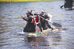 Competitors in River Ness raft race. Priests with gold crosses taking part in River Ness Raft race in aid of the Charity Children 1st held on 16th August 2014 royalty free stock photo