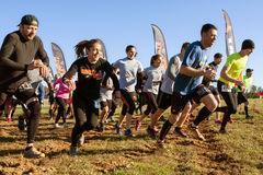Competitors Sprint From Start Line At Obstacle Course Race. Buford, GA, USA - November 21, 2015:  Competitors take off running from the start line of the Muddy Royalty Free Stock Photography
