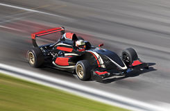 Competência de carro de corridas F1 em uma trilha com borrão de movimento Fotos de Stock
