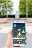 Compiegne, France. 7th August 2016. Pokemon Go on a smartphone with a blurred WWII war memorial in the background. The game has be. Picture of a hand holding a royalty free stock images