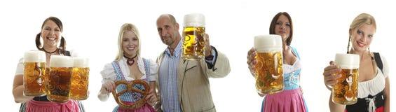 Compilazione delle cameriere di bar di Oktoberfest e di una coppia Fotografie Stock