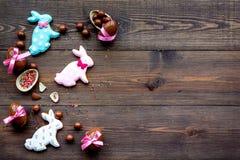 compisition пасха Подарок помадки пасхи Яичка шоколада около печений в форме зайчика пасхи на темной деревянной предпосылке Стоковые Фото