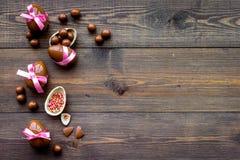 compisition пасха Подарок помадки пасхи Яичка шоколада около печений в форме зайчика пасхи на темной деревянной предпосылке Стоковое Изображение RF