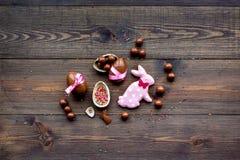 compisition пасха Подарок помадки пасхи Яичка шоколада около печений в форме зайчика пасхи на темной деревянной предпосылке Стоковые Изображения
