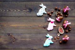 compisition пасха Подарок помадки пасхи Яичка шоколада около печений в форме зайчика пасхи на темной деревянной предпосылке Стоковая Фотография