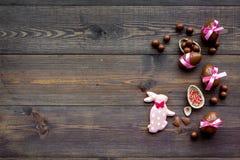 compisition пасха Подарок помадки пасхи Яичка шоколада около печений в форме зайчика пасхи на темной деревянной предпосылке Стоковое Фото