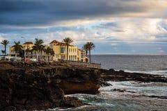 Compita al océano y a la orilla rocosa con los edificios en puesta del sol foto de archivo libre de regalías