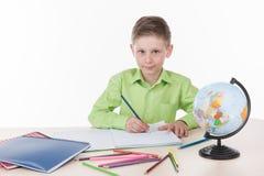 Compito caucasico di scrittura del ragazzo dello studente Fotografia Stock