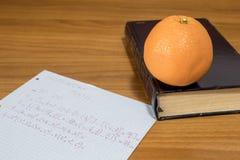Compito di per la matematica con un libro e una frutta arancio su una tavola di legno Fotografie Stock Libere da Diritti
