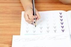 Compito di scrittura della mano del bambino Fotografie Stock Libere da Diritti