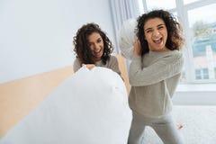 Complètement des amis d'énergie combattant avec des oreillers Images stock