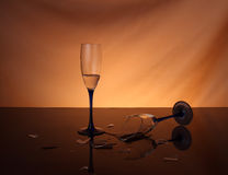 Complètement du vin et des verres à vin cassés au-dessus du fond orange Photos libres de droits
