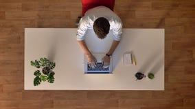 Complétez en bas du mâle de laps de temps de tir dans le bureau en bois utilisant l'ordinateur portable tout en se reposant au bu clips vidéos