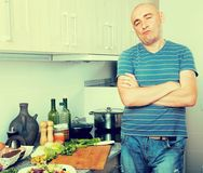 Positive guy stands proudly in kitchen hands clasped stock images