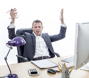 Complaining businessman sitting at office, raising annoyed hands for exasperation. Complaining middle aged businessman sitting at his office, raising annoyed Royalty Free Stock Image
