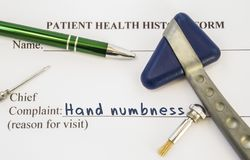 Complaint hand numbness. Patient health history is on table of neurologist, which contains complaint hand numbness surrounded by n royalty free stock photography