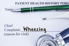 Complaint of wheezing. Paper health history form, which is written on the patient`s chief complaint of wheezing, surrounded by a s. Tethoscope, electronic Royalty Free Stock Photos