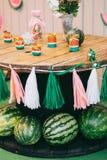 Compleanno di legno con le angurie, decorazione di festa del ` s dei bambini della tavola di picnic dei nastri bianchi e rosa e d immagini stock libere da diritti